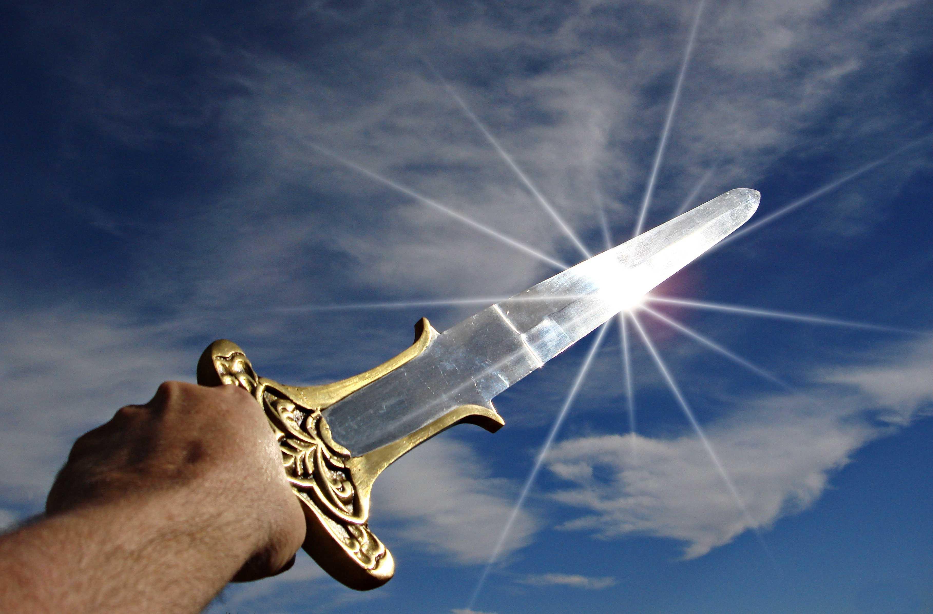 Hand reckt blitzendes Schwert zum Himmel