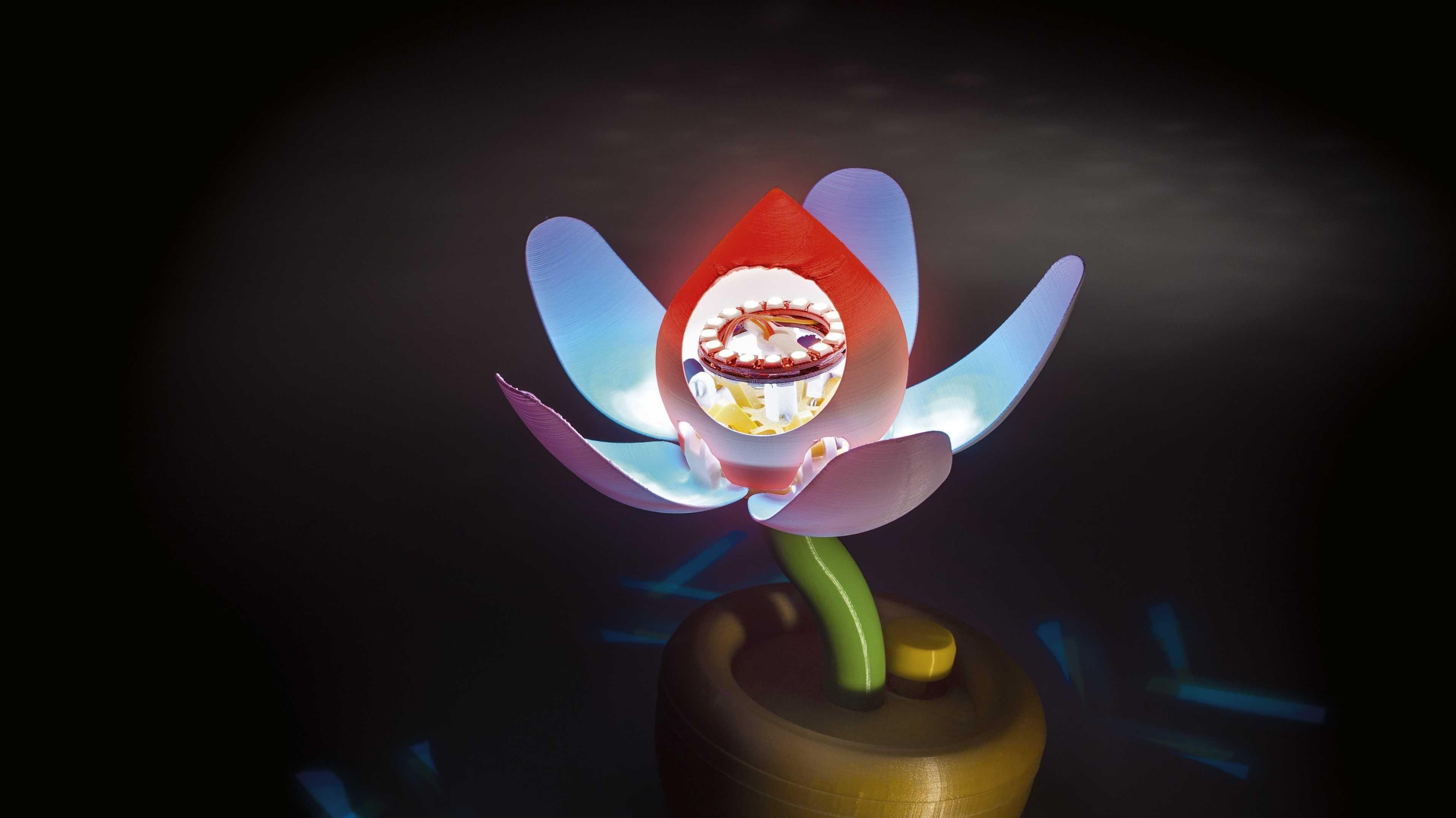 Eine Blume aus dem 3D-Drucker mit blau beleuchteten Blättern und rot beleuchteter Blüte