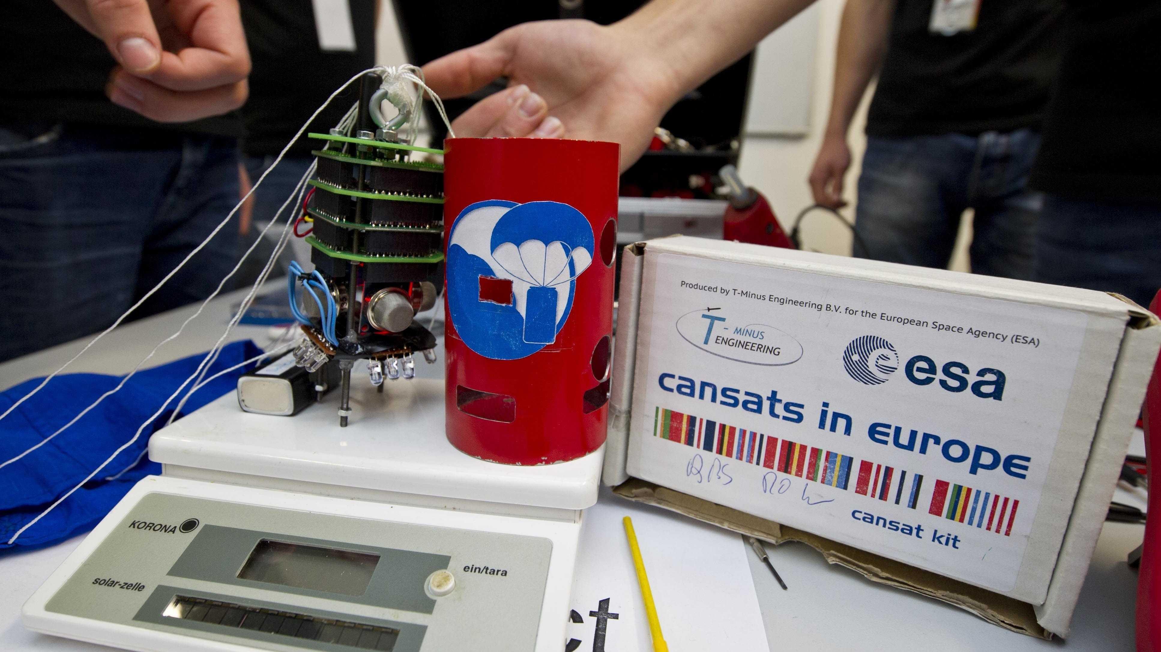 Eine rot-blau-weiße Satelittenhülle in Form einer Getränkedose und ihr elektronisches Innenleben auf einer Waage