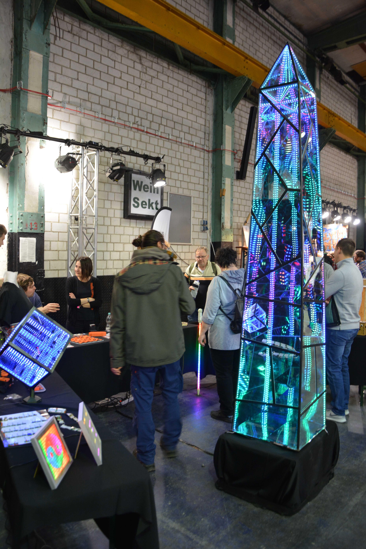 Ein Obelisk aus Spionspiegelglas und LED-Streifen, der weit über einen Mann hinausragt, der daneben steht.