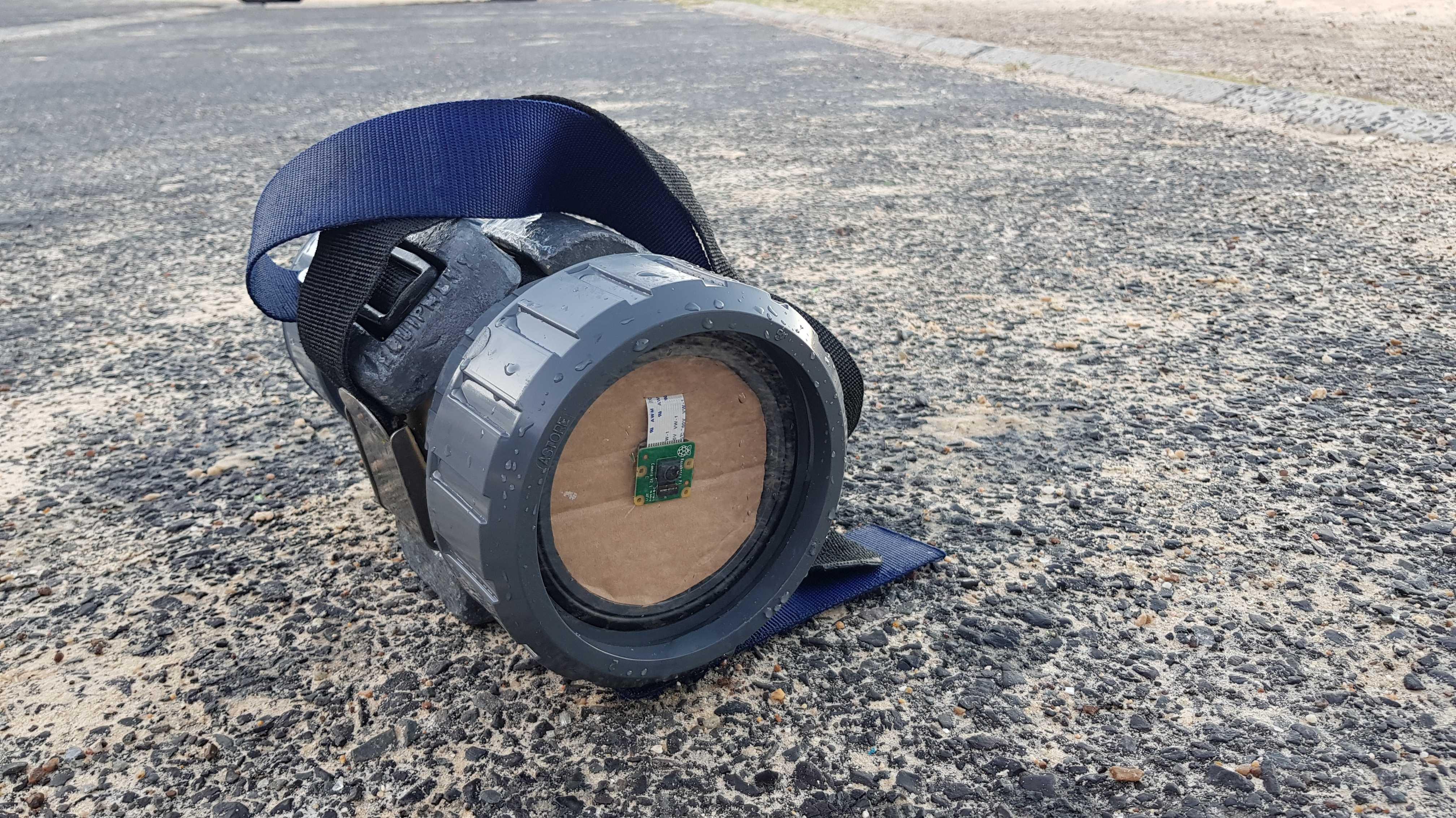 Auf einem steinigen Boden liegt ein Gerät, das an eine Taschenlampe erinnert. Vorn ist allerdings eine grüne Platine auf einem Stück Pappe befestigt.