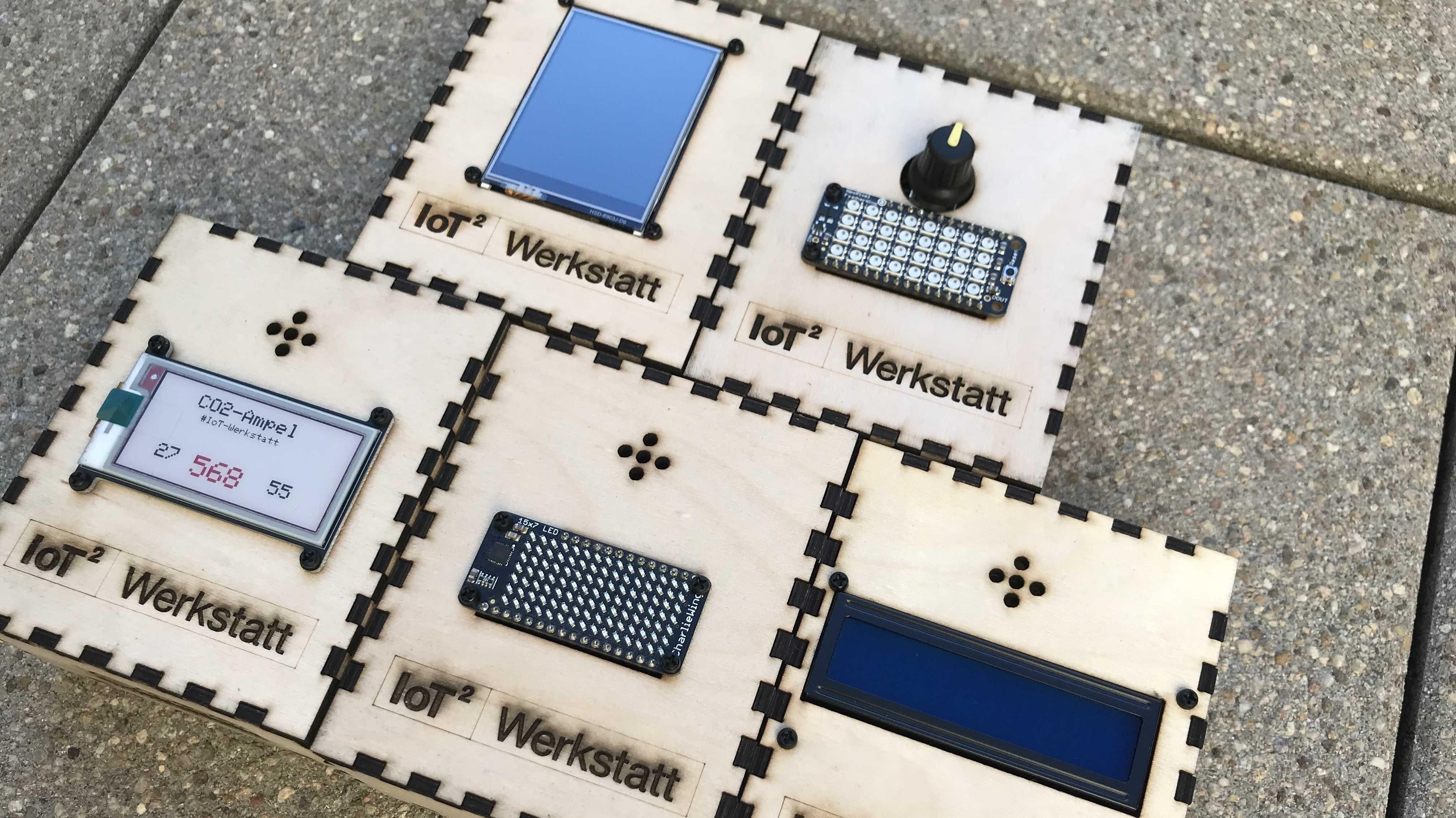 Nebeneinander liegen fünf CO2-Ampeln aus Holz, mit unterschiedlichen Displays, wie E-Paper und Adafruit Charlieplex Featherwing.