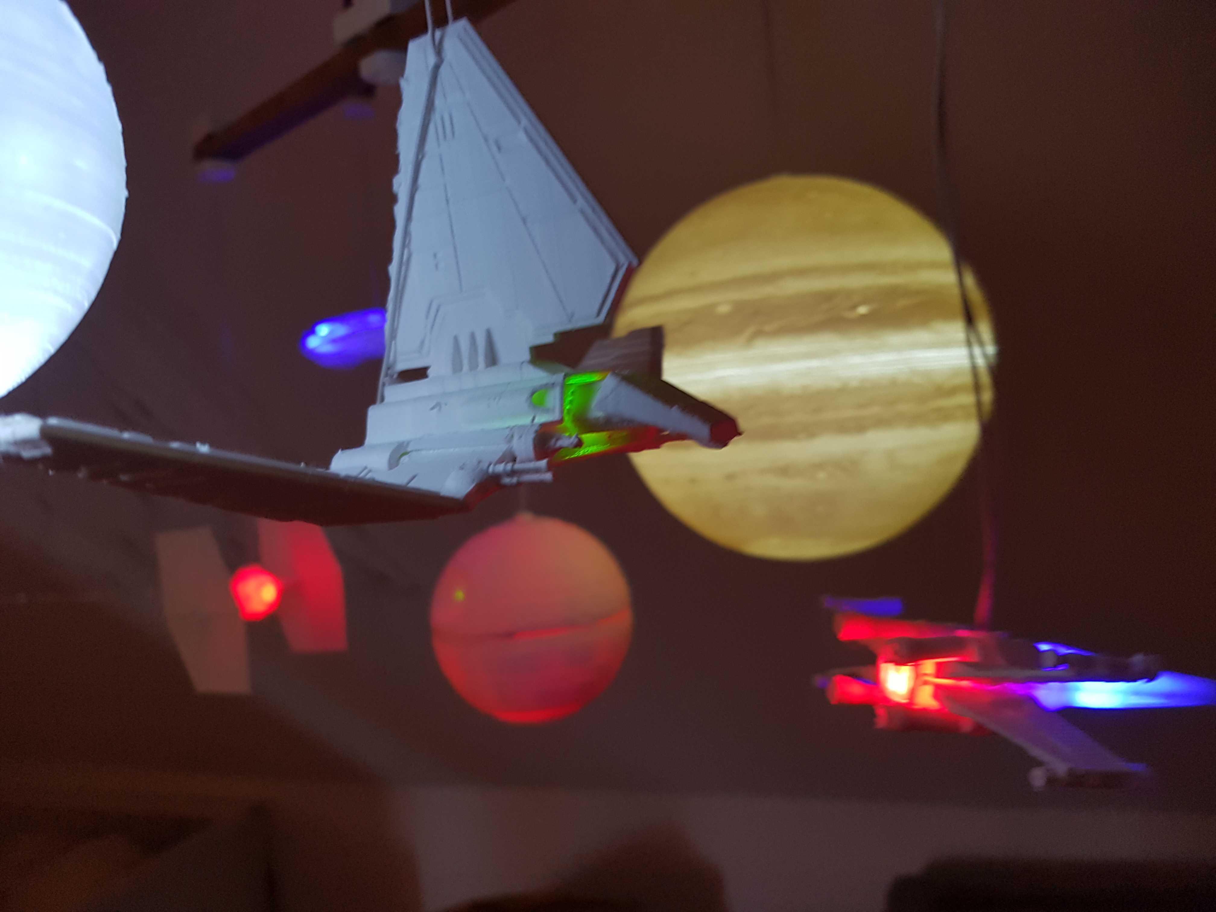 Mobile mit beleuchteten Raumschiffen und Planeten