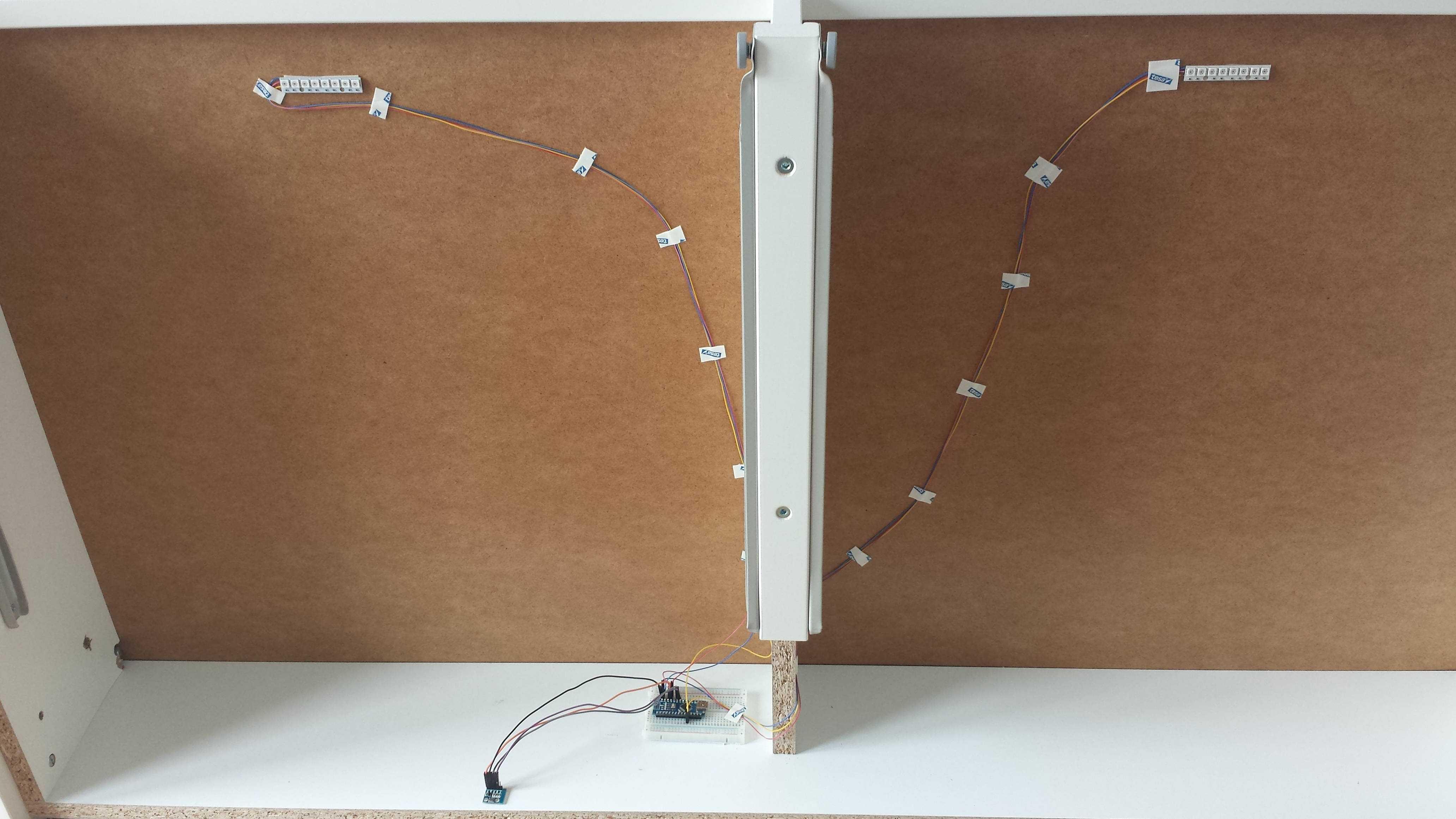 Zwei LED-Streifen unter einem Babybett, deren Kabel zu einem Steckbrett mit Arduino führen