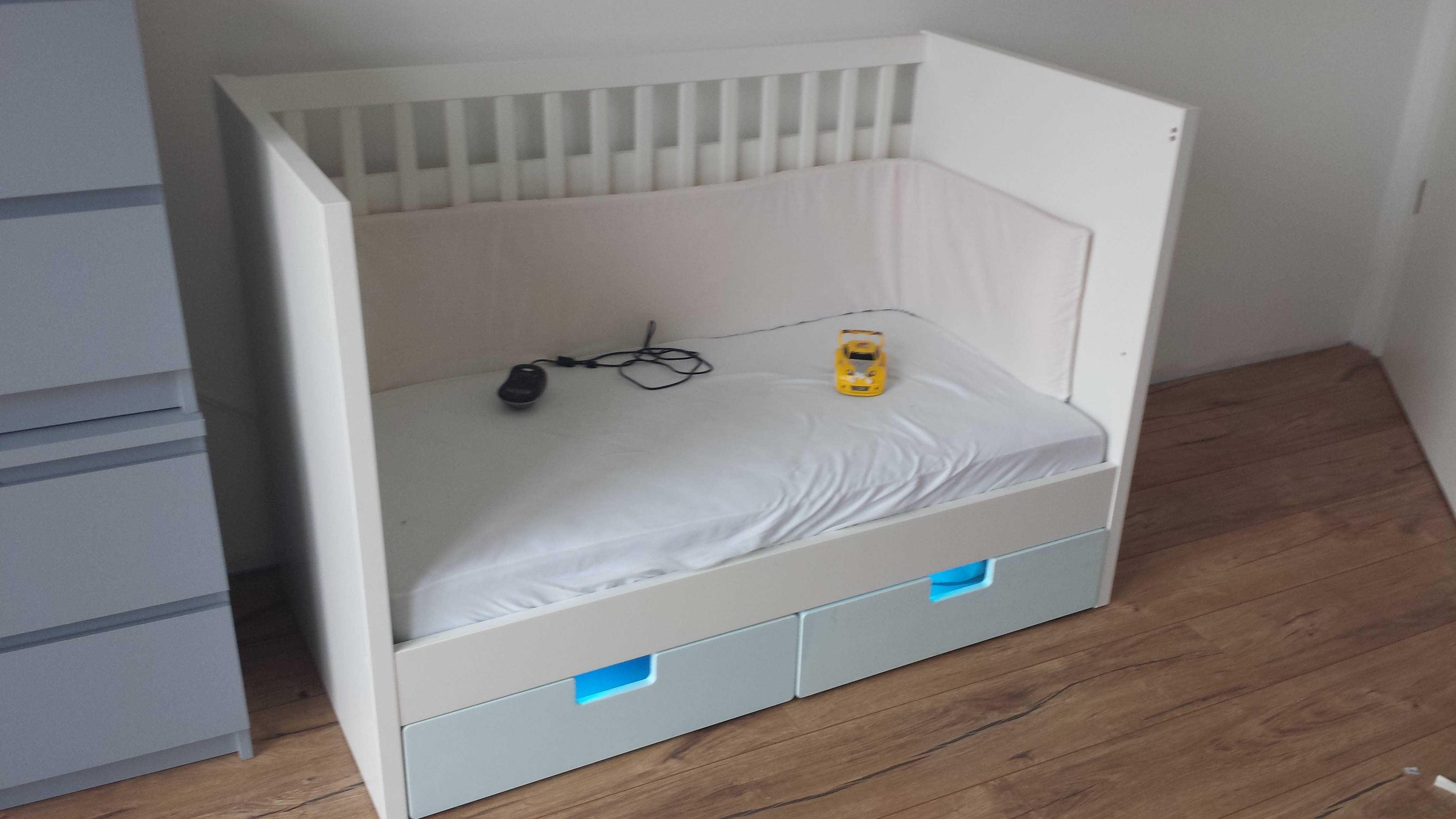 Ein weißes Babybett, aus dessen Unterbettkiste es türkis leuchtet