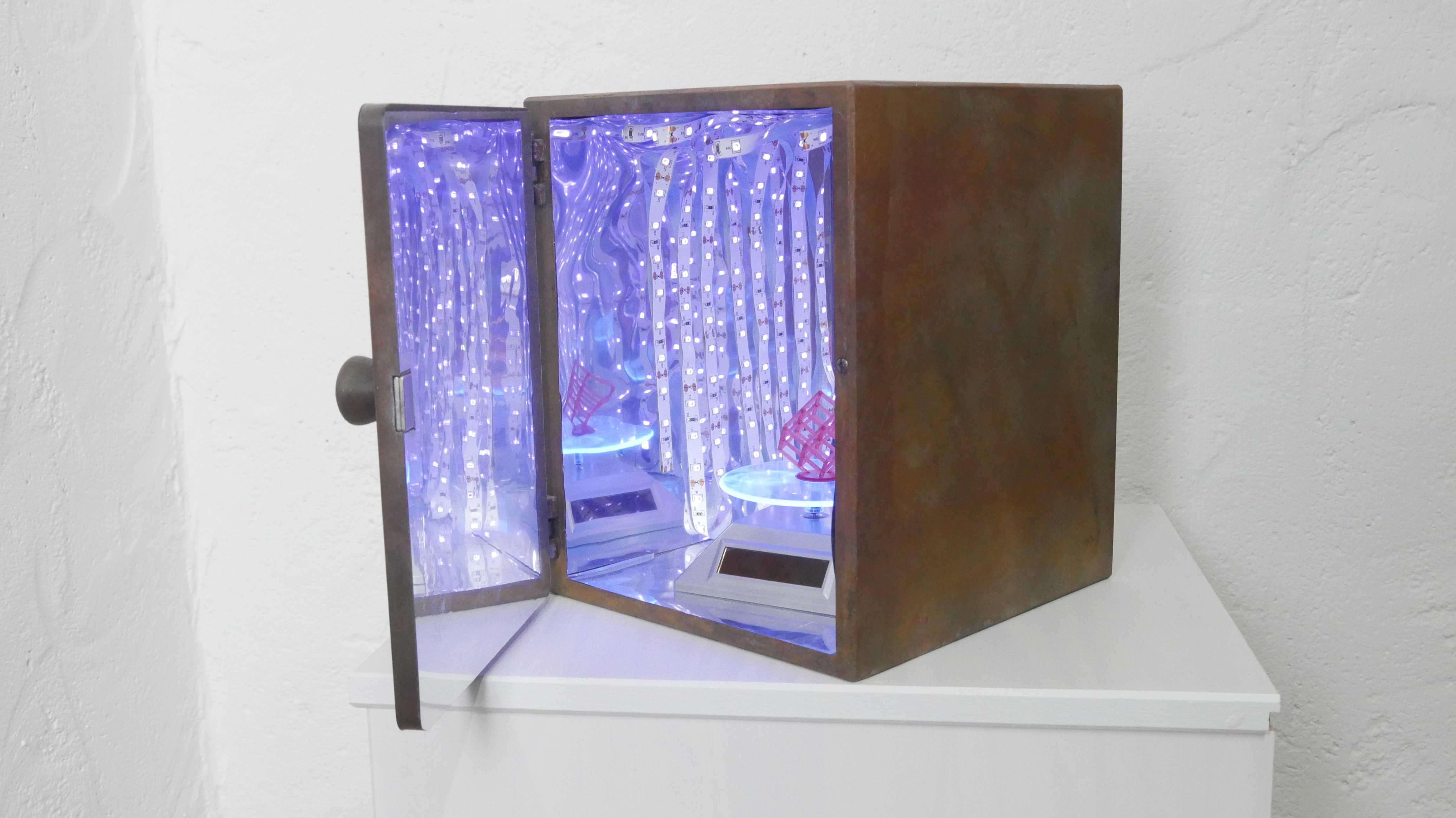 Vor einer weißen Wand steht ein Holzkasten mit geöffneter Tür. Das Innere ist spiegelnd ausgekleidet und mit LED-Streifen beleuchtet. In der Mitte der Kammer steht ein Drehteller.