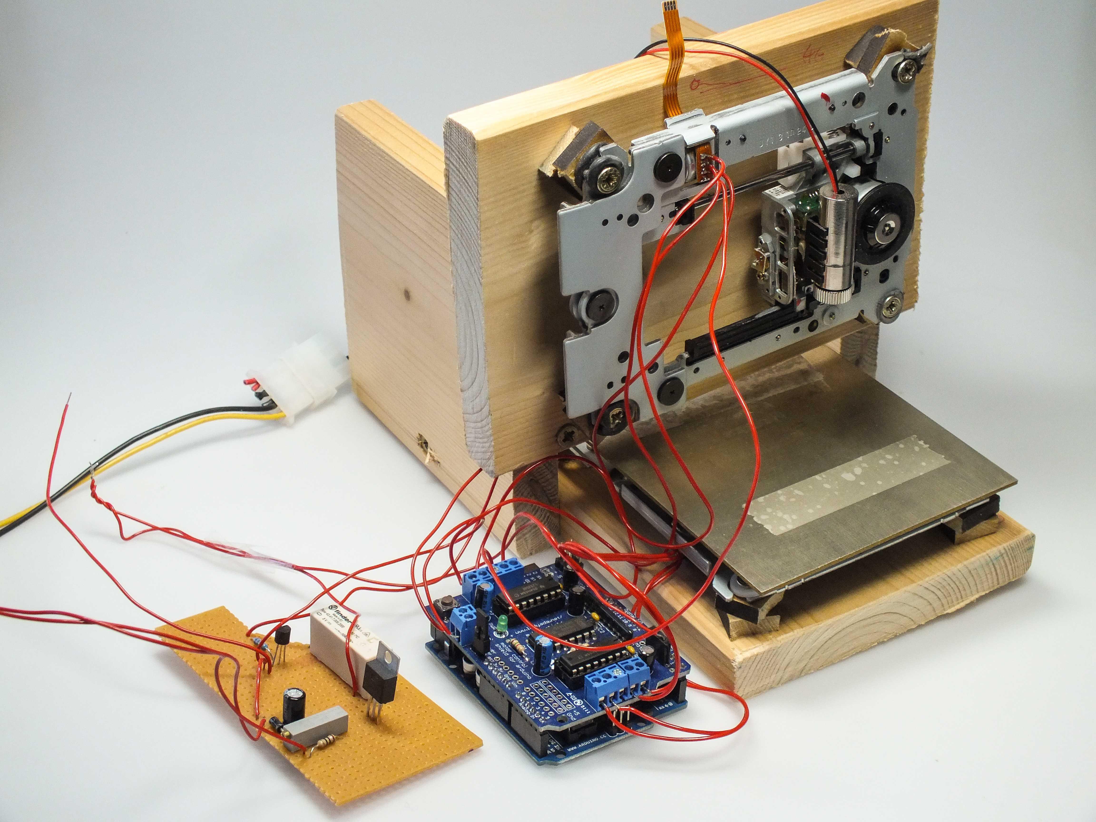Holzaufbau mit Innenleben eines DVD-Brenners, einem Arduino Uno und einer Platine.