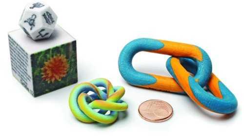 Ein Würfel, ein Dodekaeder und ein Regenbogenknoten aus dem 3D-Drucker von 3D Systems, aus eingefärbtem Gipspulver aufgebaut. Daneben gestreifte Kettenglieder aus farbig bedruckten und verklebten Papierschichten