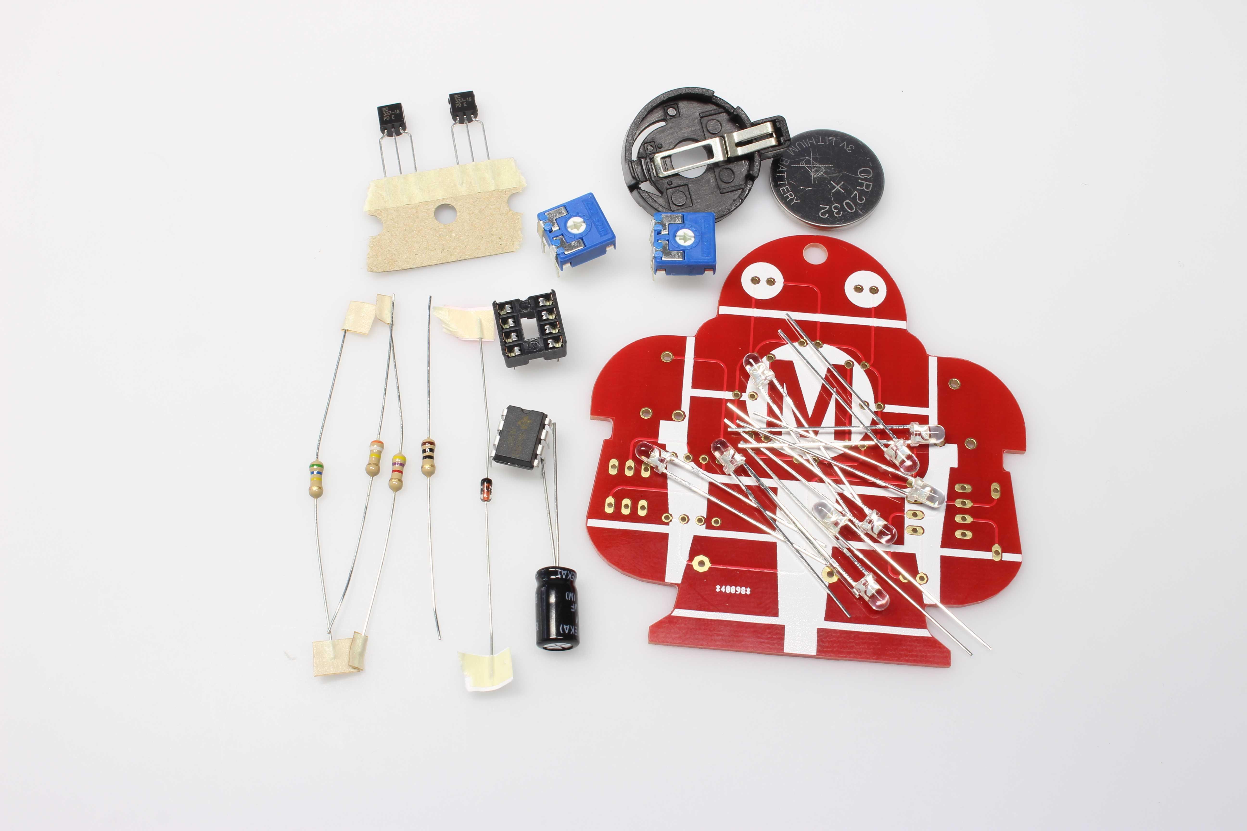 Löt-Makey: Eine rote Platine in Roboterform mit elektronischen Bauteilen