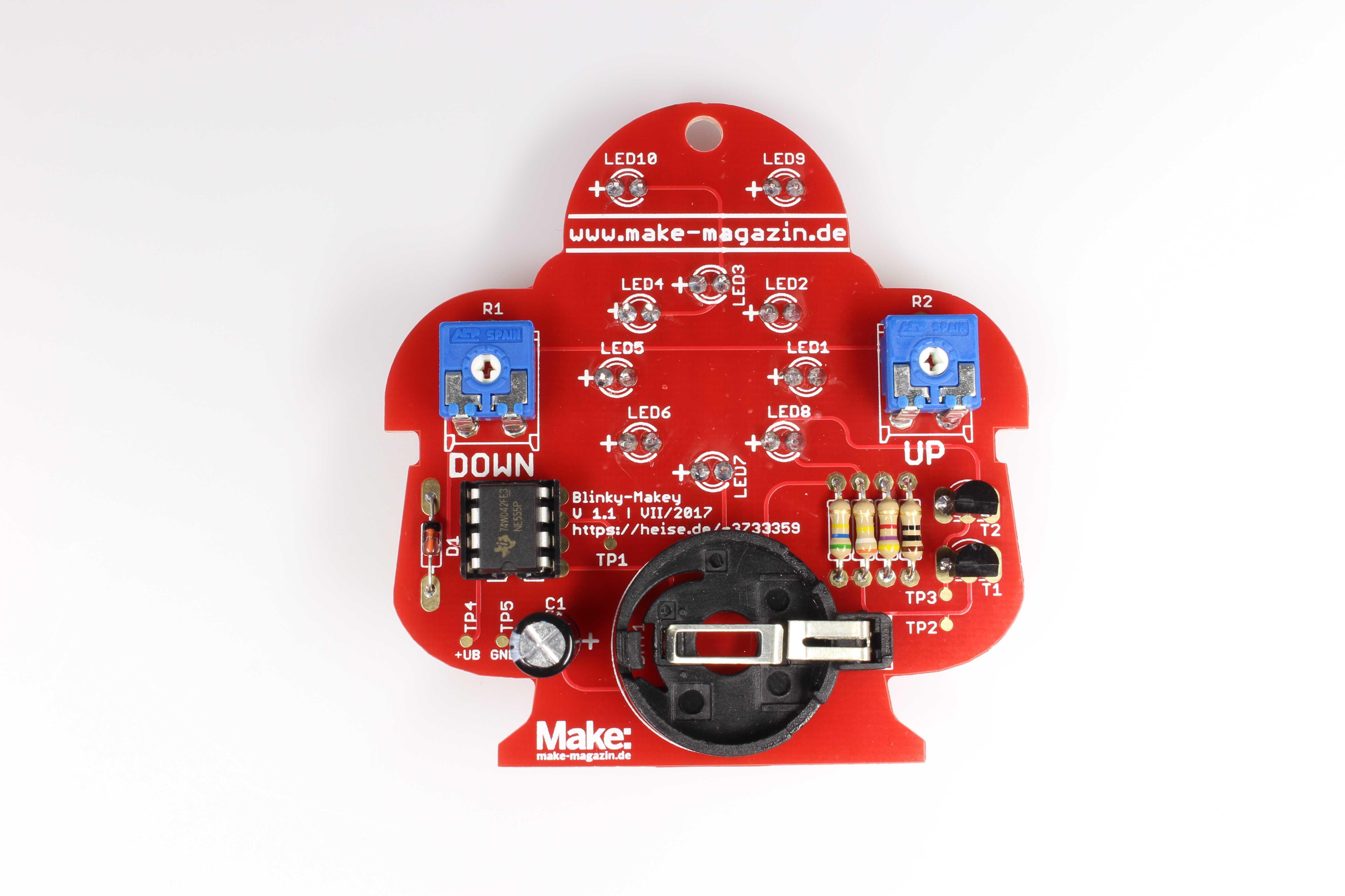 Löt-Makey von hinten: Eine rote Platine in Roboterform mit Lötstellen
