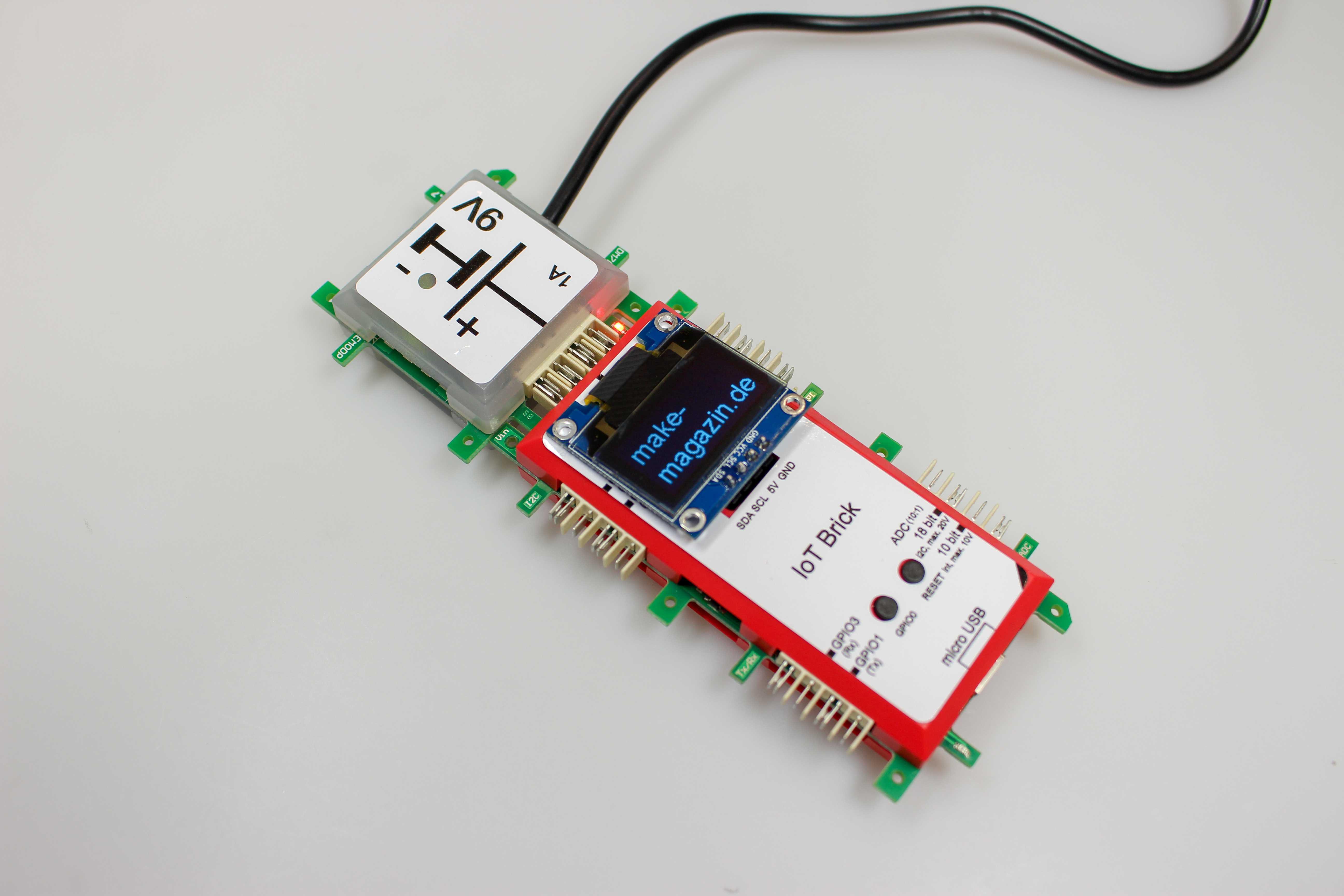 Ein roter Plastikquader mit dunklem Display, angesteckt ein grünes Quadrat mit Kabel