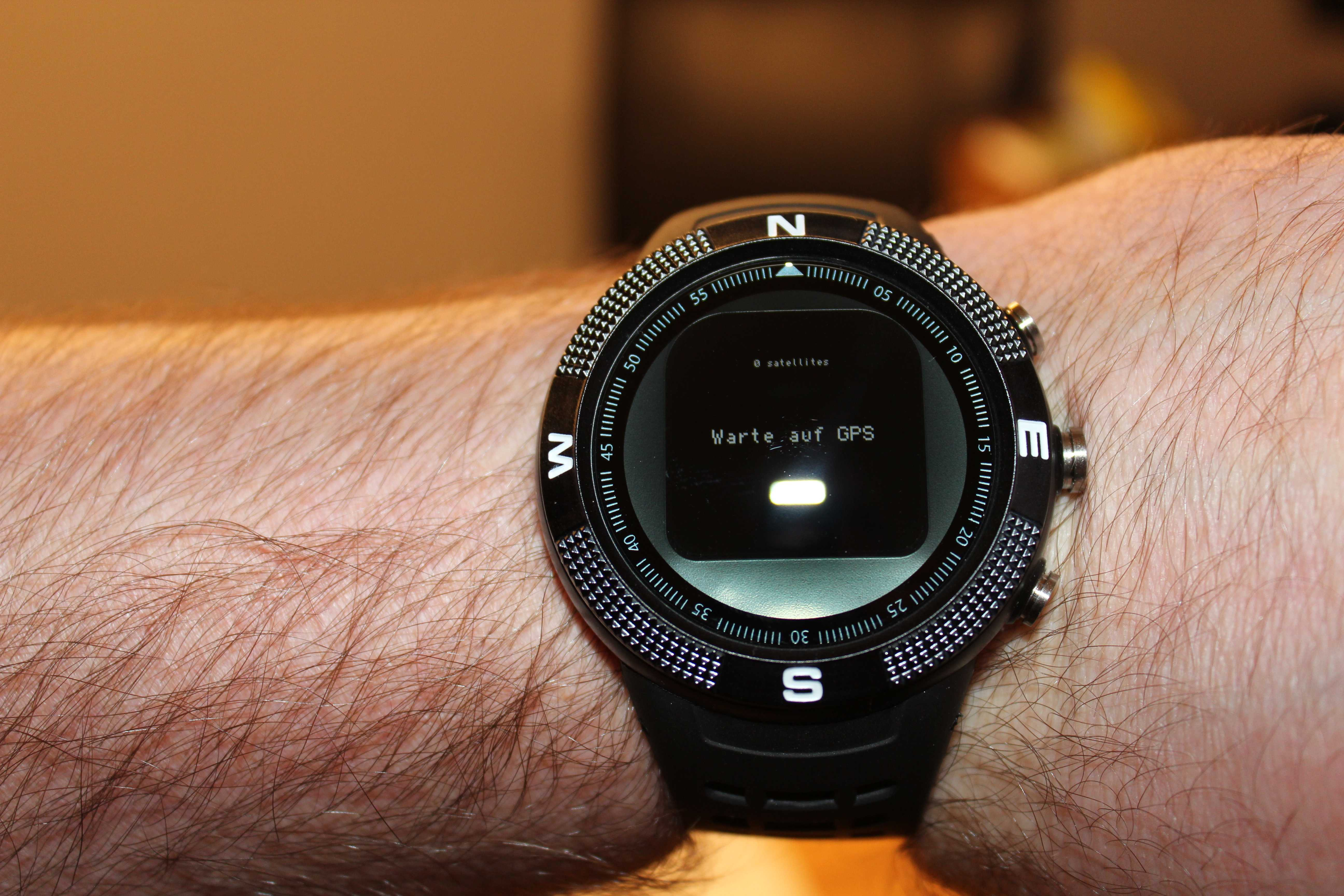 Eine Arm, der eine schwarze Smartwatch am Handgelenk trägt. Auf dem Display steht: Wait for GPS.