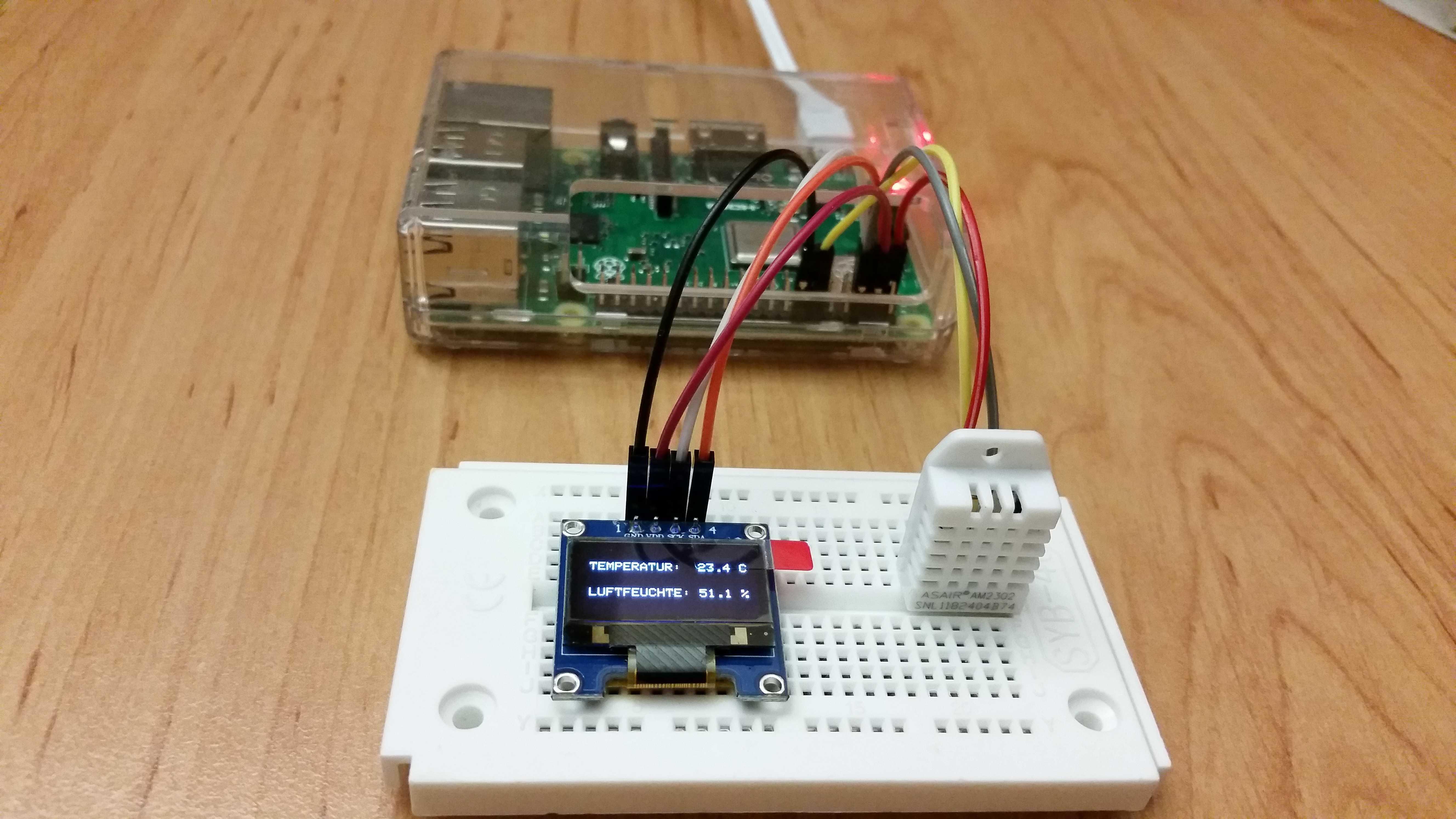 Raspberry Pi neben Breadboard mit Temperatursensor und OLED, auf dem die aktuelle Temperatur angezeigt wird.