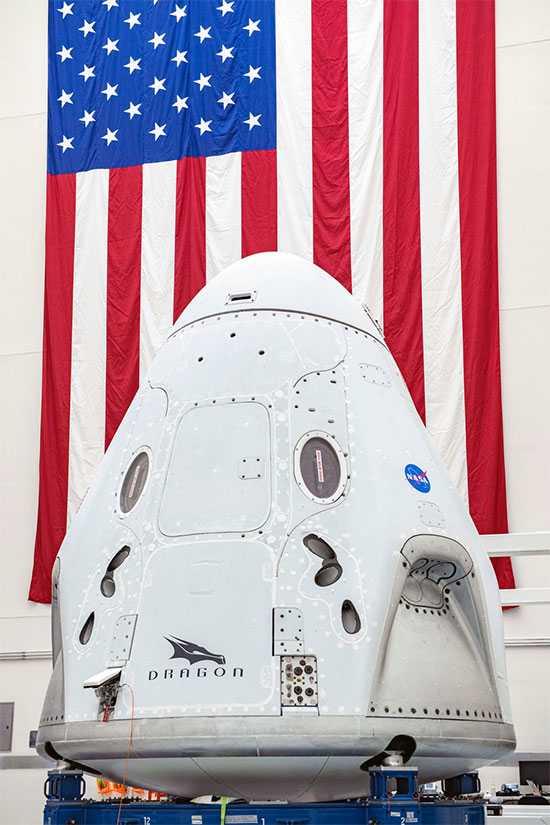 Raumkapsel Crew Dragon, dahinter US-Flagge