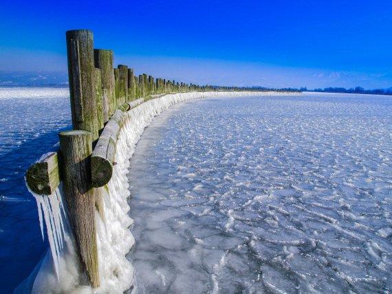 Zaun im See von Pit Zwerger
