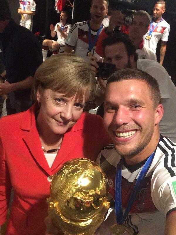 Lukas Podolski nahm sich, den WM-Pokal und die Bundeskanzlerin mit auf ein Foto