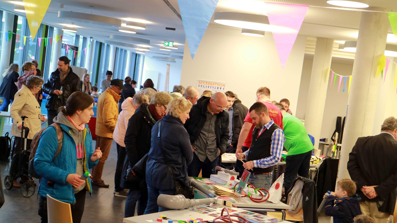 Blick in die Hochschule Rhein-Waal während der Mini Maker Faire 2019 mit vielen Menschen an verschiedenen Ständen.