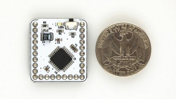 Auf weißem Hinergrund liegt ein weißes, quadratisches Elektronikboard neben einem US-amerikanischen Vierteldollar
