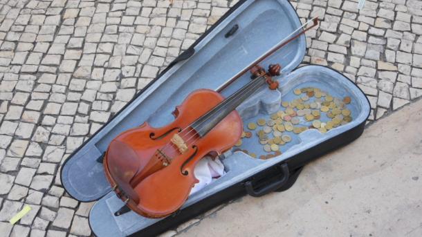 Geigenkasten mit Violine und vielen Münzen