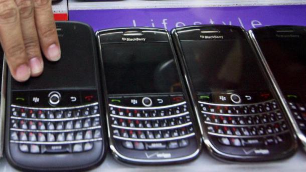 Eine Hand greift nach einem von 3 Blackberrys