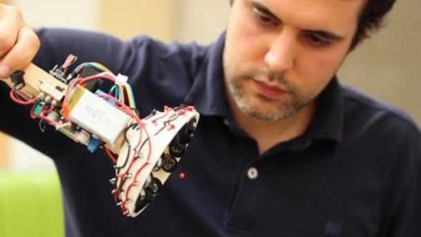 Ein Mann hält ein Gerät mit vielen Kabeln, das an eine Taschenlampe erinnert