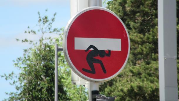 """Verkehrszeichen """"Ausfahrt einer Einbahnstraße"""" mit zusätzlich aufgemalter Figur, die quasi den weißen Querbalken auf der Schulter schleppt"""