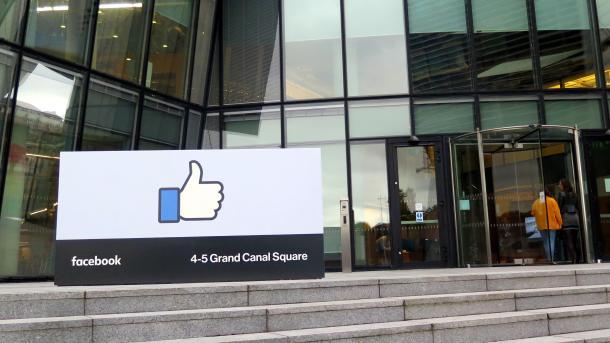 """Glaspalast, davor ein großes Schild mit """"Like""""-Daumen"""