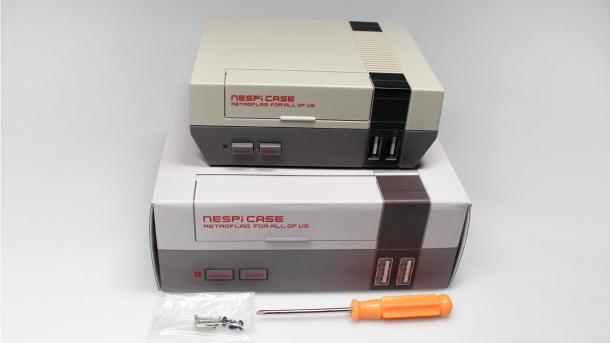 Das NESPi Case, ein grauer Plastikkasten, über einer Pappverpackung im NES-Stil, daneben liegen Schrauben und ein Schraubendreher
