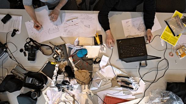 Ein Schreibtisch mit viel Papier, Laptops und vier Händen