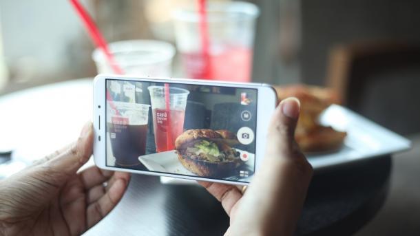 Handy fotografiert Teller mit Essen und Becher
