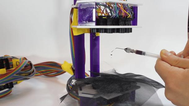 Ein Tropfen schwarzer Flüssigkeit schwebt zwischen zwei Arrays mit Ultraschallwandlern