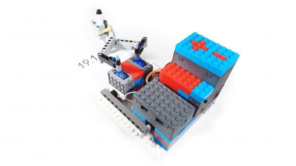 Ein bunter Lego-Aufbau hält mit zwei Ärmchen einen Stift, der die Uhrzeit schreibt