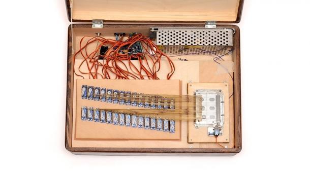 Blick in einen Holzkasten mit vielen Servos, die mit schmalen Metallstreifen eine Spieluhr erklingen lassen