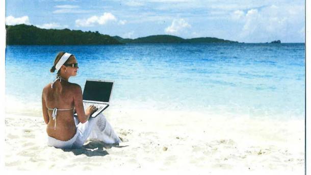 Fesche Dame mit Laptop am Strand