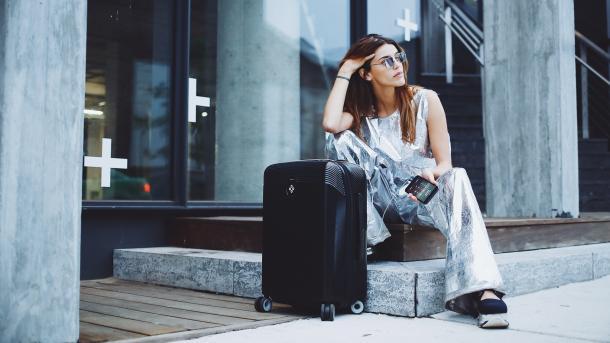 Frau sitzt neben Koffer vor einem Gebäude