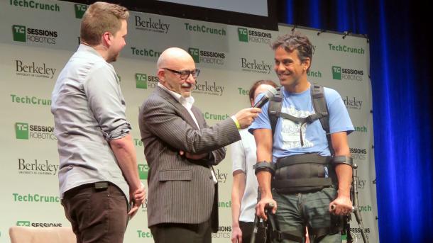 3 Männer auf einer Bühne, davon einer mit Krücken und Exoskelett