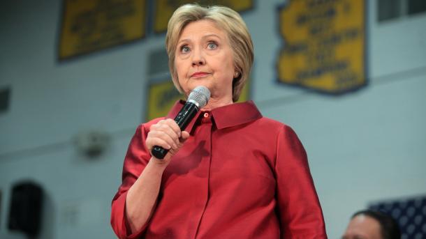 Hillary Clinton in rotem Anzug mit Mikrofon