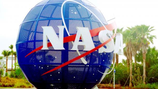 Blaue Kugel mit NASA-Schriftzug, dahinter Palmen