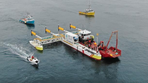 Plattform wird von Schiffen in Stellung gebracht, 4 Turbinen stehen waagrecht zur Wasseroberfläche