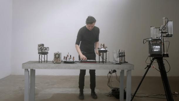 Moritz Simon Geist hinter einem Tisch mit Musikrobotern