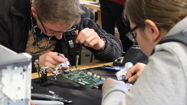 Zwei Kinder beugen sich über Elektronik