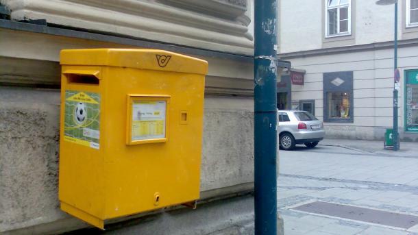 Gelber Briefkasten an Hauswand