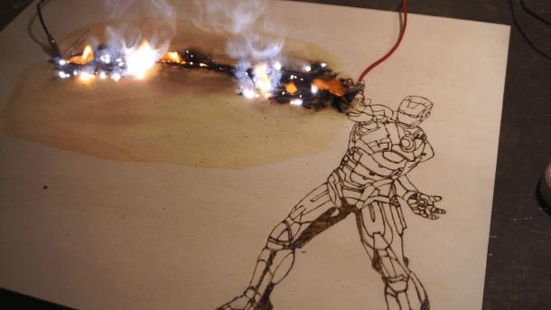 Holzbrettchen mit Iron Man, an seiner Hand ist ein Kabel angelegt, von dem aus sich eine Flamme durch das Holz brennt.