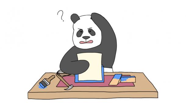 Panda vor einem Schreibtisch mit Papier, Hammer und Holzstücken.