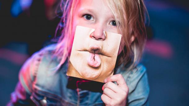 Kind hält sich Foto eines Mundes eines Erwachsenen vor den Mund