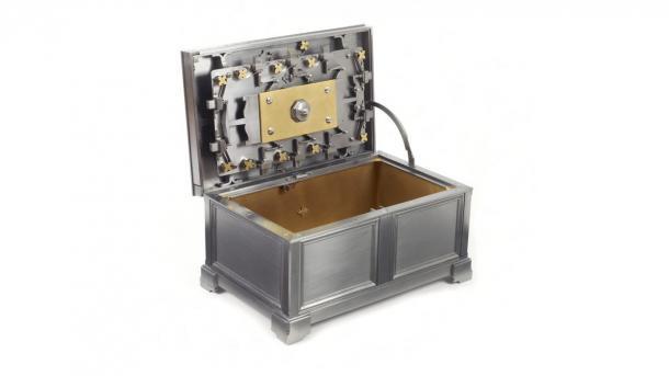 Aufgeklappte Kiste aus Metall mit ausgeklügeltem Verschluss-Mechanismus im Deckel.