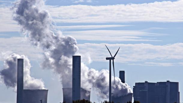 Windrad, dahinter Kühltürme eines Kohlekraftwerks