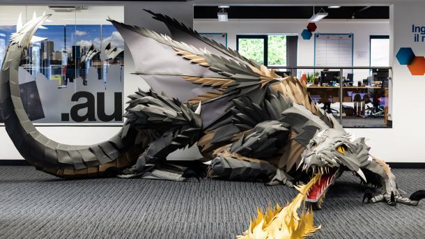 Ein grauer Drache aus Papier steht in einem Büro und spuckt Feuer.