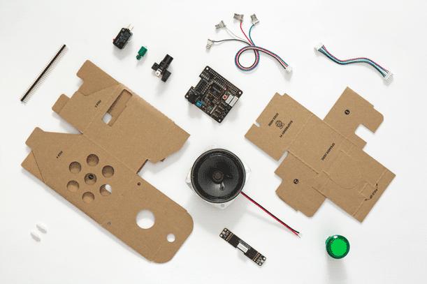 Pappteile und elektronische Bauteile liegen einzeln auf einer weißen Fläche
