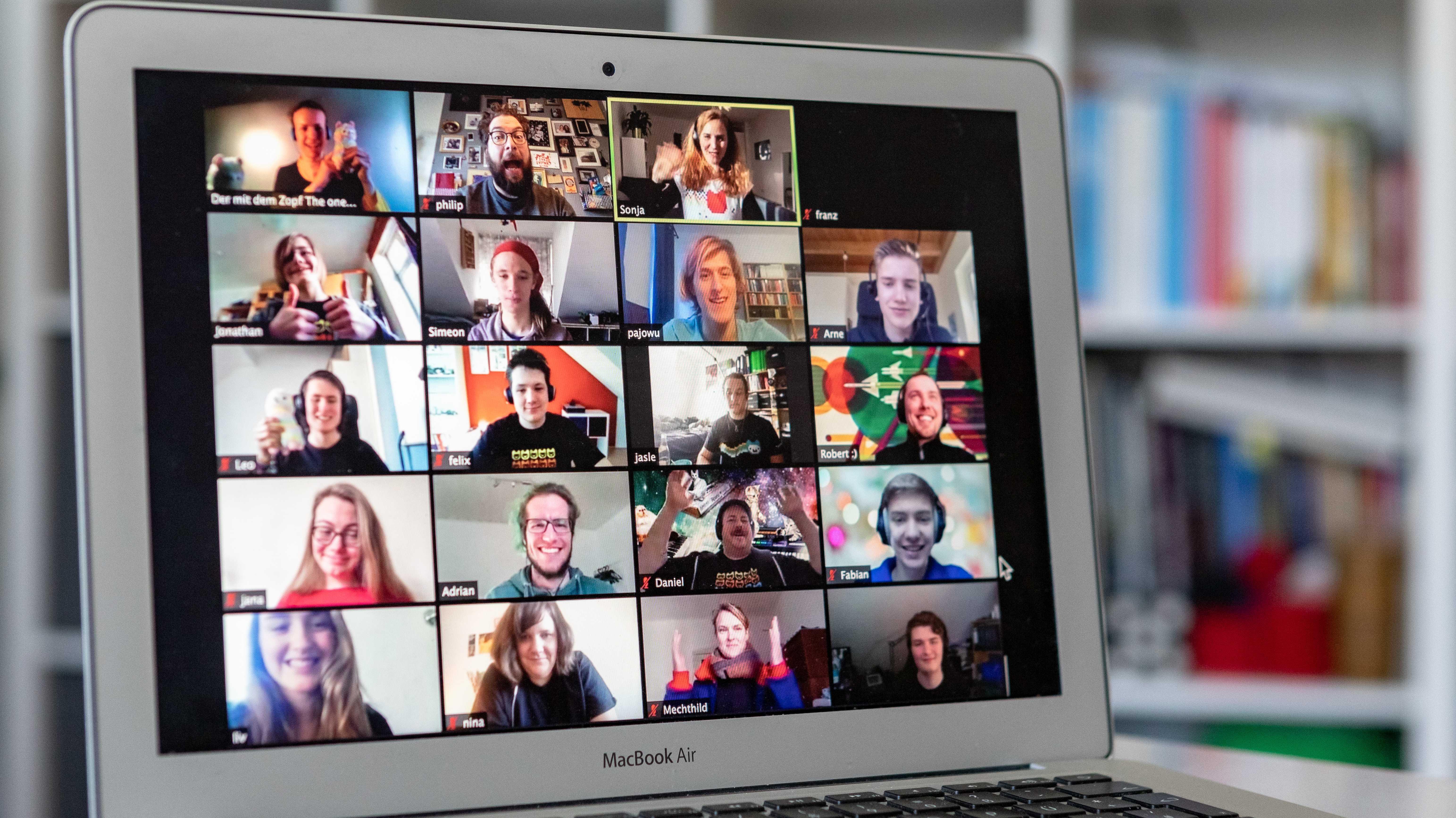 Blick auf einen Laptop-Monoitor, auf dem viele Gesichter einer Videokonferenz zu sehen sind.